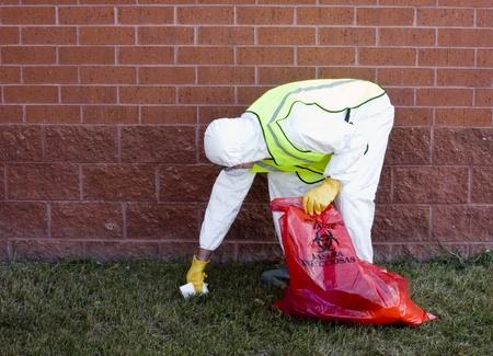 hazardous waste: man in protective suit picking up hazardous waste