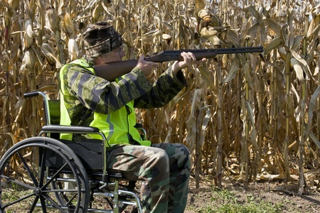 disabled hunter in a safety vest shooting a shotgun in a corn field