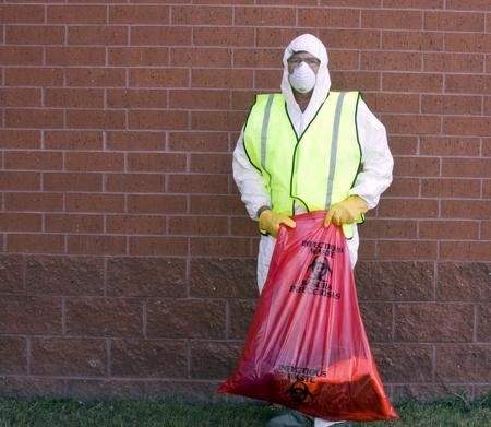 hombre en un traje de protecci�n el manejo de residuos infecciosos Foto de archivo