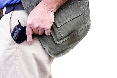 concealed: man pulling a concealed weapon from his pocket isolated over a white background  Stock Photo