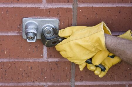 plumber repairing an outdoor water faucet on a brick wall