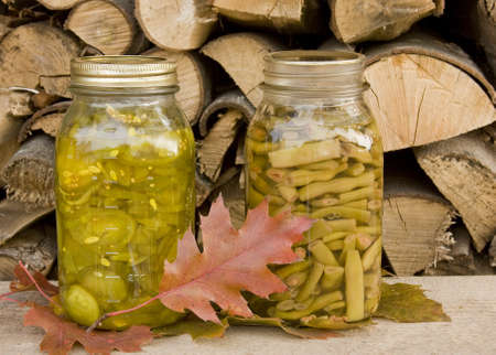 pickled: canned pickles and beans with a fall background of leaves and firewood