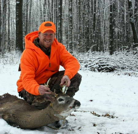 hunter in safety orange with a whitetail deer harvested against a snow and tree background