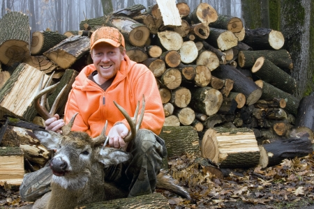 deer hunter in blaze orange with a ten point whitetail trophy buck with a wood pile in the background