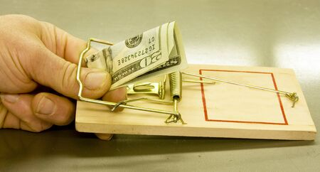 trap: persons hand caught in a mouse trap taking a twenty dollar bill