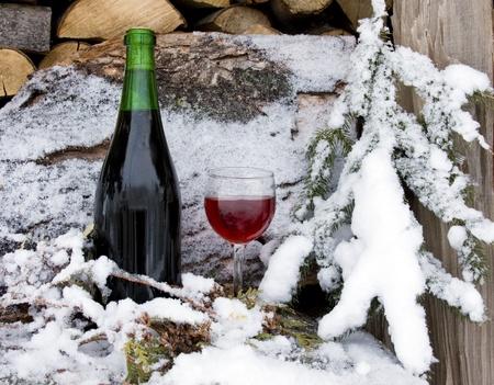 botella y copa de vino por la nieve en una pila de madera de le�a