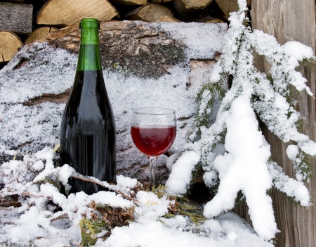 bottle and glass of wine chilled by snow on a wood pile of firewood