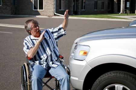 man in een rolstoel geraakt door een auto Stockfoto