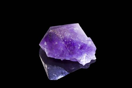 gemology: amethyst crystal with reflection over a black background
