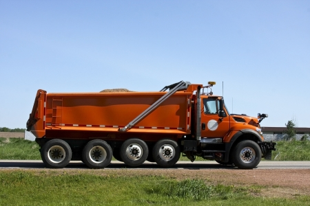 orange dump truck loaded going down a highway