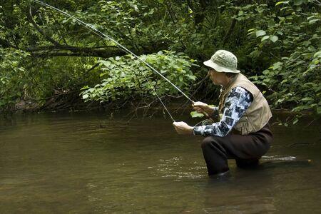 waders: pescador en una rodilla llevando botas de pecho en un arroyo con �rboles para el fondo