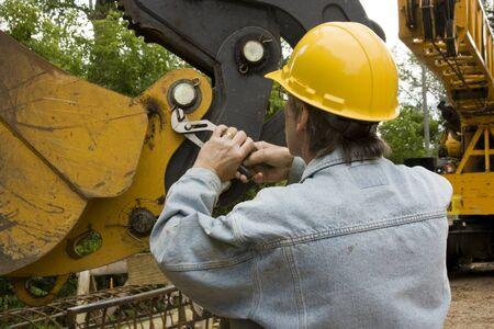 alicates: mecánico de equipo pesado que llevaba un sombrero amarillo duro la reparación de una grúa con herramientas de mano
