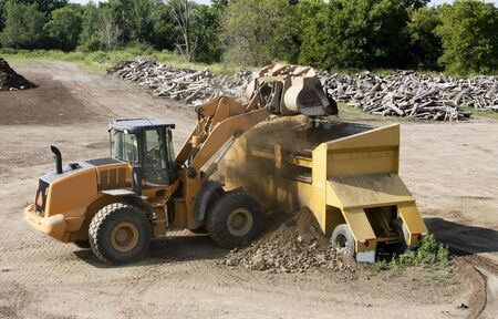loader: front end loader adds soil to a screening machine