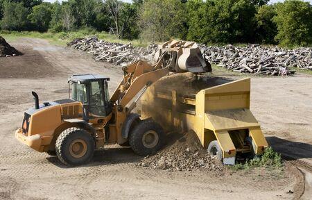 front-end loader voegt bodem tot een zeefmachine