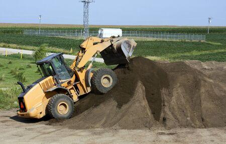 front loader: cargador frontal poner tierra encima de un montículo