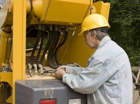 zwaar materieel monteur repareren van hydraulische slangen Stockfoto