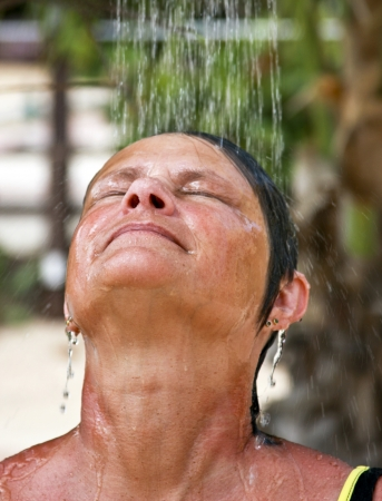 rinse: woman in a swimsuit rinsing off under a beach outdoor shower Stock Photo