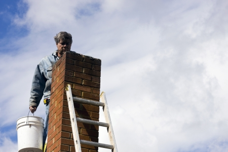 brick mason on a ladder repairing damaged chimney
