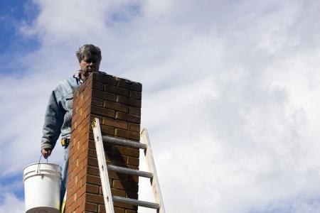 metselaar op een ladder repareren van beschadigde schoorsteen Stockfoto