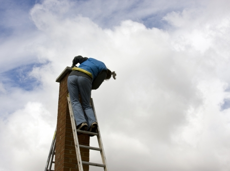woman on a high extension ladder cleaning a brick chimney Stock Photo
