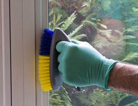 housekeeping worker cleaning a window frame with a scrub brush