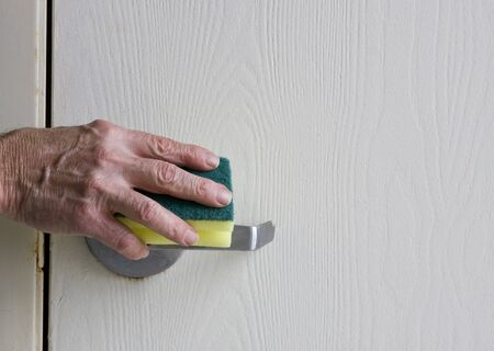 door handles: housekeeping worker cleaning a stainless door handle with a sponge