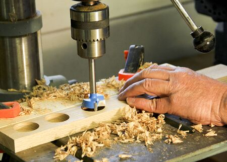 wholes: flush mounted drill bit in a drill press making wholes in a cabinet makers board Stock Photo