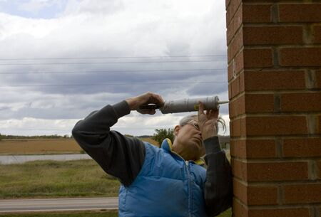 woman on a ladder repairing a brick chimney 版權商用圖片