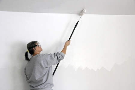 ceiling: woman worker painting a ceiling with a roller
