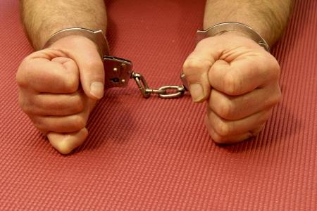 Manette su un polso prigionieri su uno sfondo opaco di gomma Archivio Fotografico - 17999380