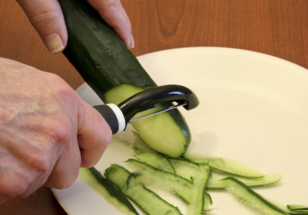 chef peeling a cucumber over a white plate