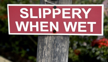 slippery: slippery when wet sign on a wooden post Stock Photo