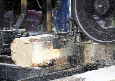 zaagsel en chips vliegen als een houtzagerij snijdt hout in boards