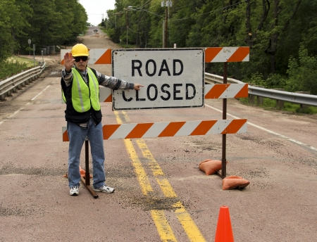 road worker: flag man points to a road closed sign on a highway