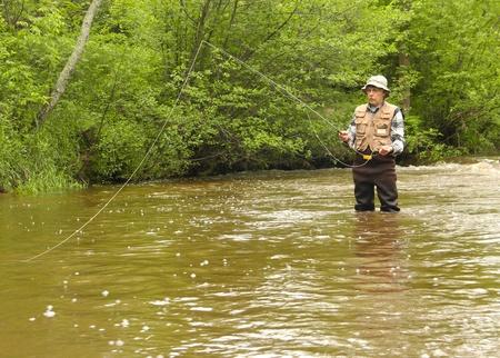 waders: wisconsin pescador de truchas en aves zancudas en una corriente de agua dulce tierra adentro Foto de archivo