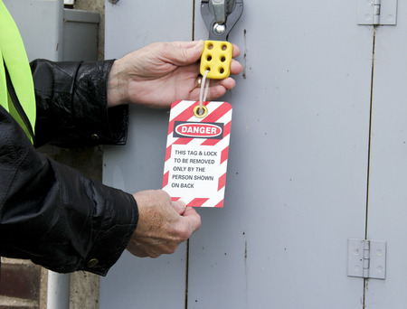 electrical panel: electrician locks out an electrical panel with a tag out sign.