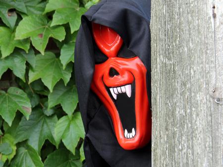 spooky mask peeking around a pole