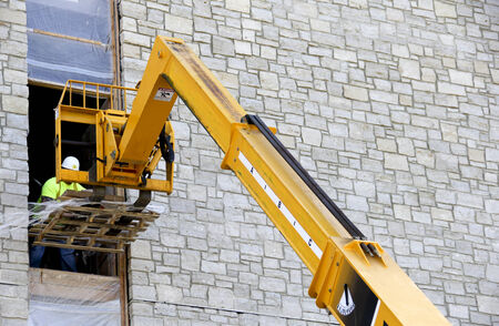 construction worker unloading supplies from a boom lift