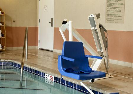 gehandicapte zwembad lift stoel over een overdekt zwembad