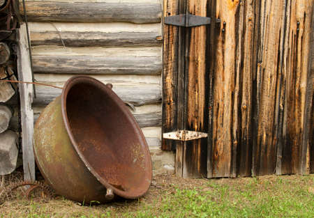Vintage cooking pot with a log cabin in the background