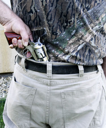 concealed: Man pulling a revolver pistol from his back. Stock Photo