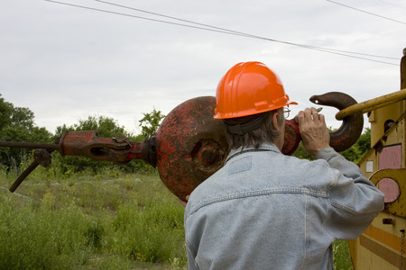 attaching: Construction worker attaching a hook to heavy equipment. Stock Photo