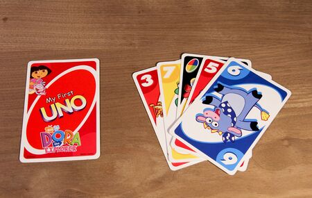 dora: SPENCER , WISCONSIN,  February, 03, 2015   Dora the Explorer UNO cards from the game showing front and back of cards. UNO is an American card game founded and invented in 1971