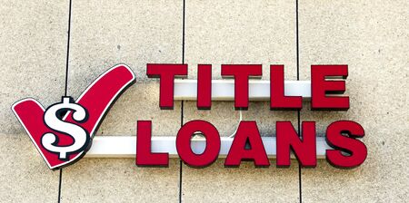lending: Title Loans Sign on a building store front.  Title Loans is a lending service that specializes in high risk loans at a high interest rate, Editorial