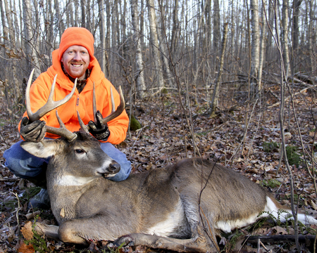 deer hunter: Happy hunter with a Whitetail trophy buck in the woods