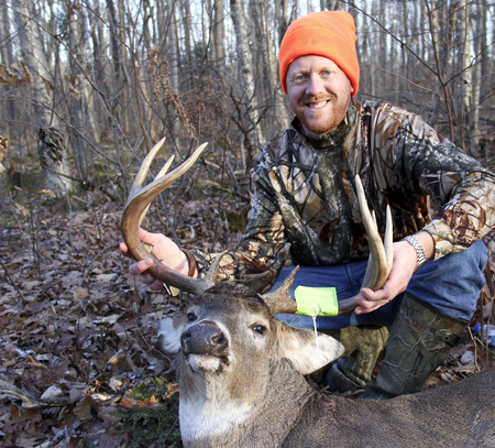 whitetail buck: Hunter with a trophy ten point whitetail buck he harvested during deer hunting