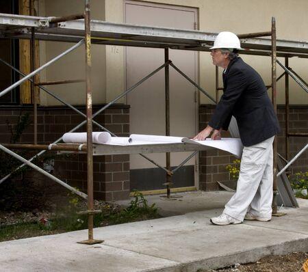 Architect with blueprints at a construction job 版權商用圖片