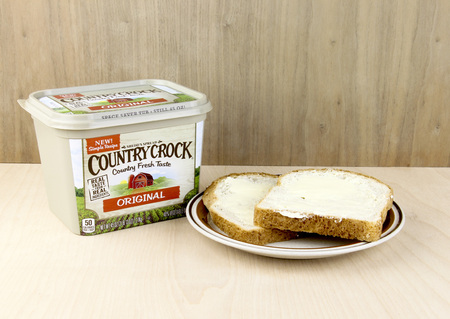 crock: SPENCER , WISCONSIN, February,1,, 2016   Container of Country Crock Vegetable Oil Spread and buttered bread     Country Crock is owned by the Unilever Company