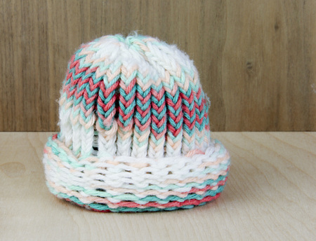 babies hands: Hand made knitted babies stocking hat from yarn over a wooden background