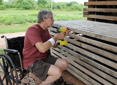 Disabled man in a wheelchair doing carpenter repair work with a cordless drill 版權商用圖片